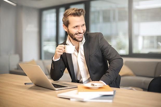 Άντρας πίνει καφέ στο γραφείο