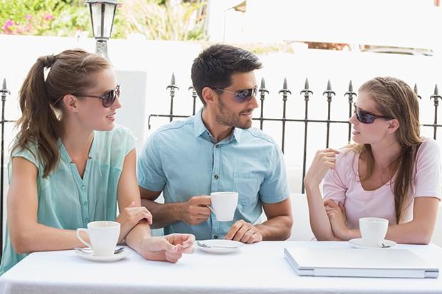 Άντρας χαμογελάει σε γυναίκες σε καφέ